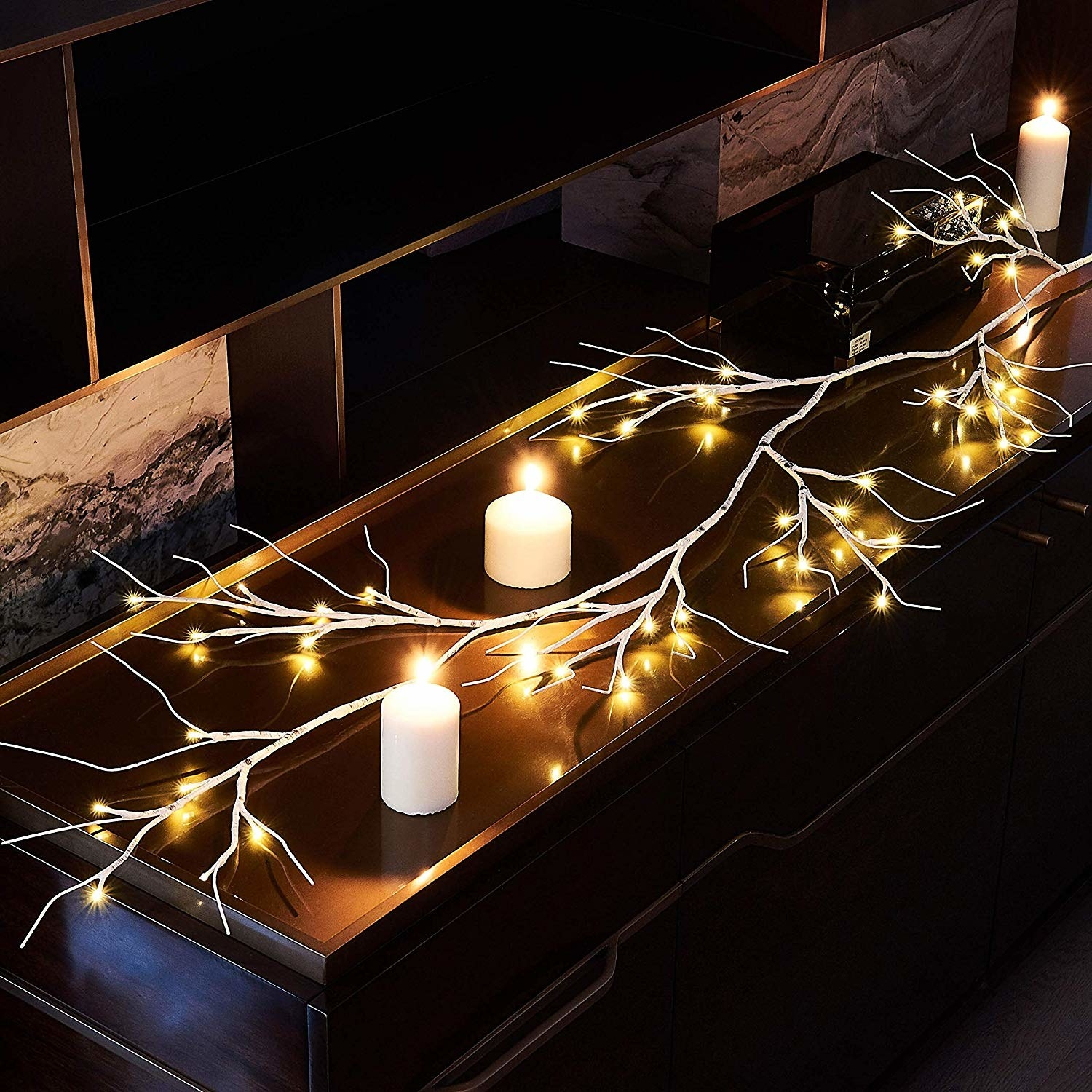 white branch speckled with individual lights on a mantle