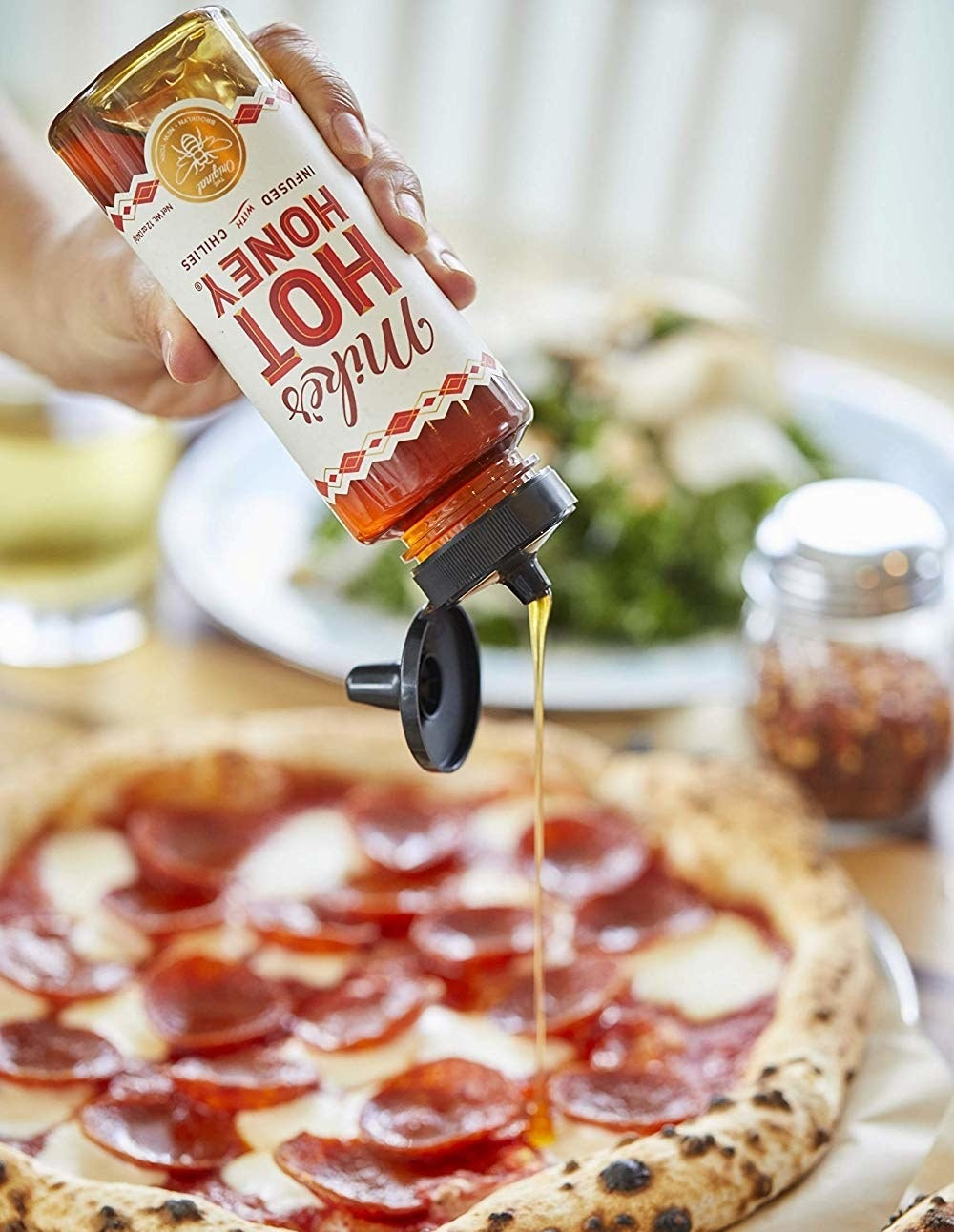 A bottle of Mike's Hot Honey being poured onto a pizza.
