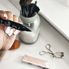 model holding the pointed felt tip end of the eyeliner pen
