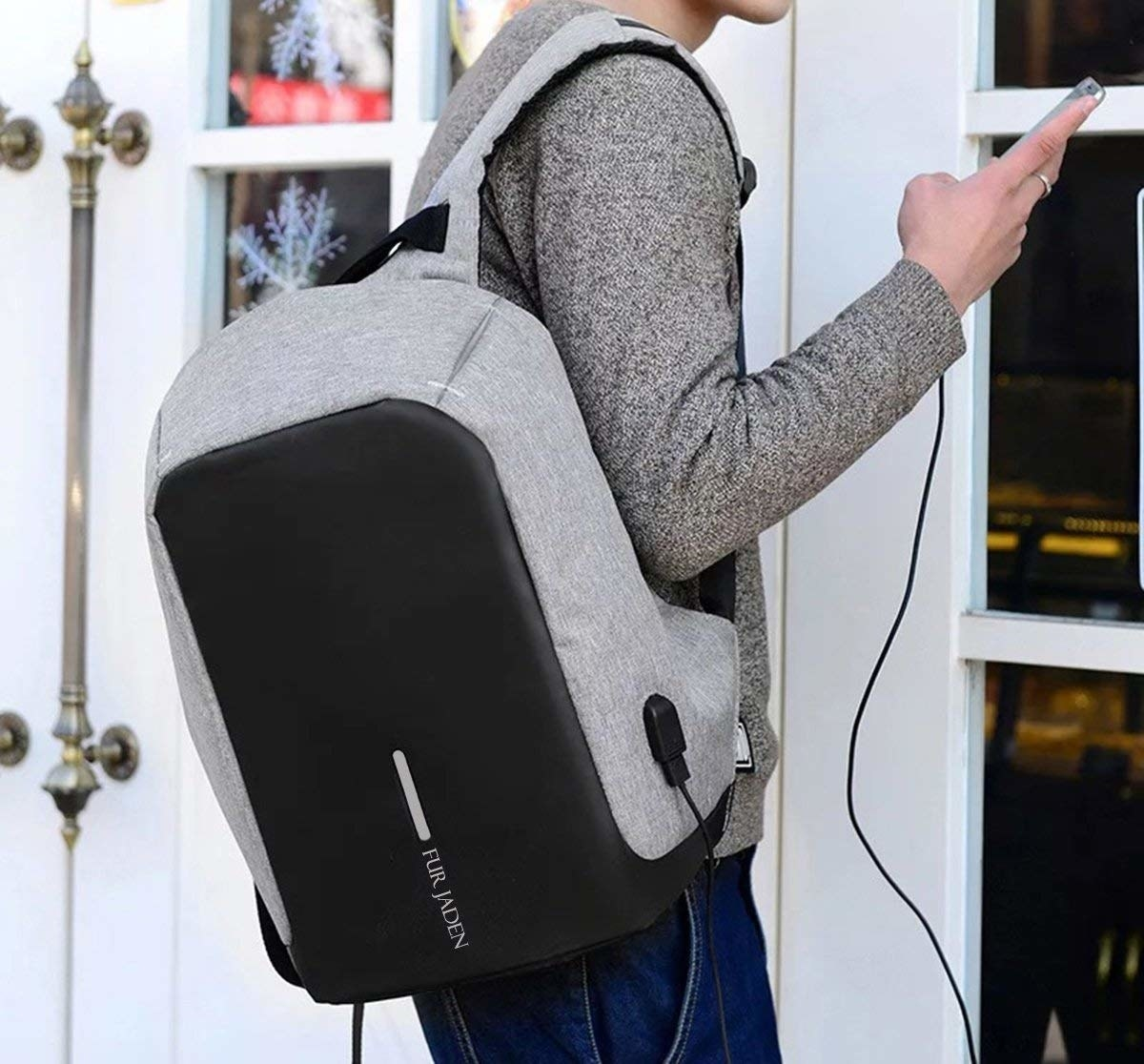 A person wearing the grey and black backpack, while a charging cable connects his phone to the bag