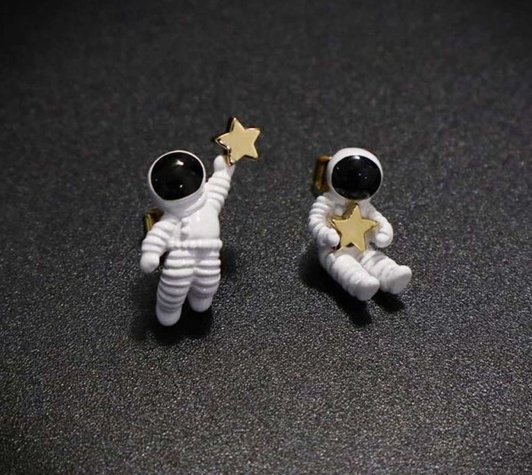 mismatched astronaut earrings holding stars