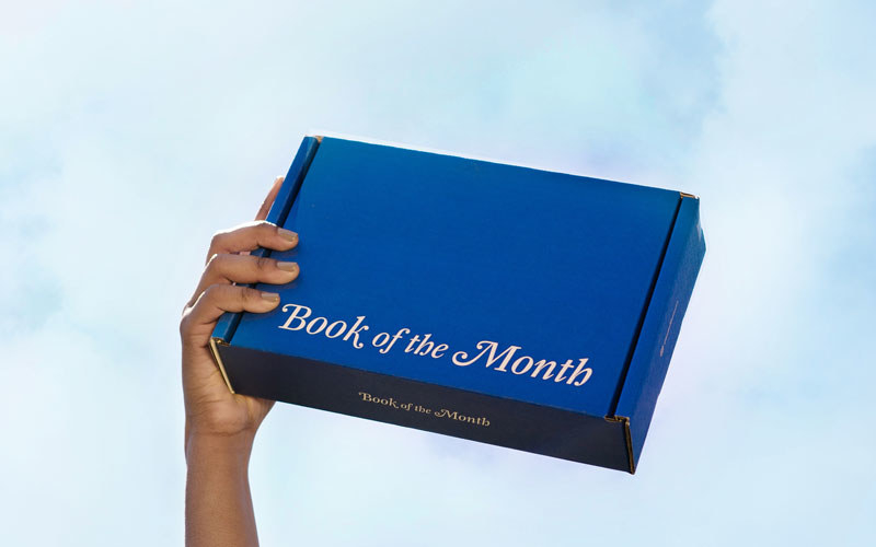 hand holding blue book of the month box