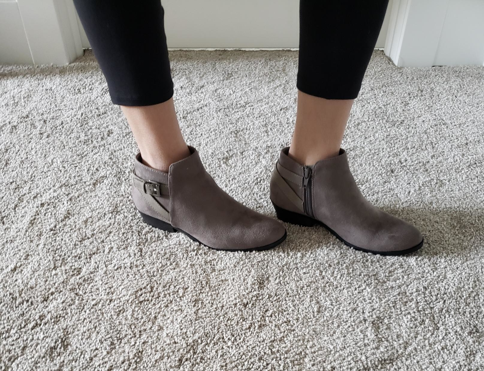 reviewer wearing the boots in grey with buckle straps around the heel