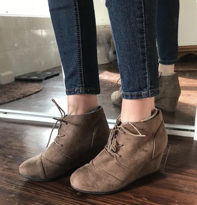 reviewer wearing the booties in brown suede