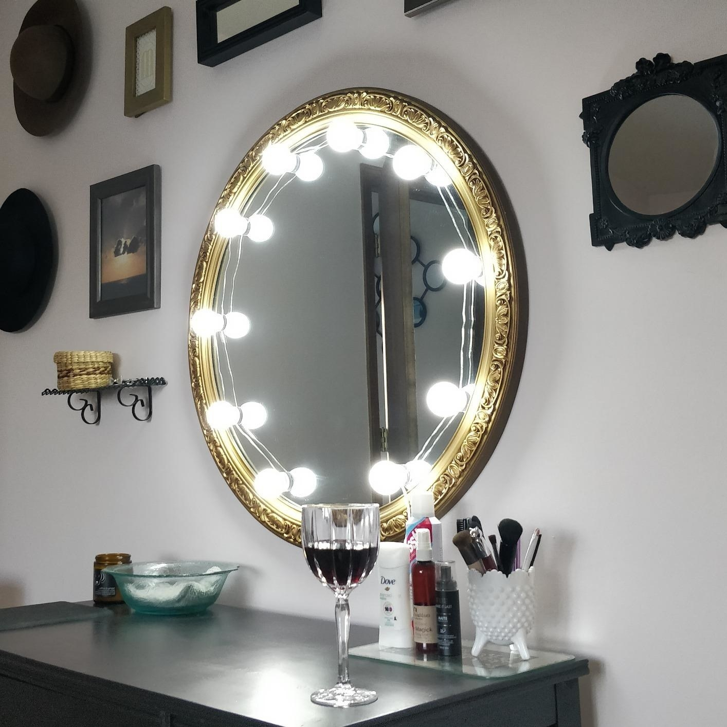 A reviewer's round mirror with the strand of globe lights placed around it