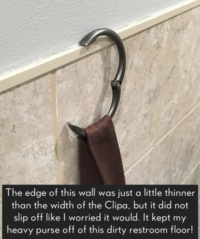 "A purse hanging from the open hook, resting on a bathroom ledge with text ""the edge of this wall was just a little thinner than the width of the clip, but it did not slip off like I worried it would. It kept my heavy purse off the dirty restroom floor"""