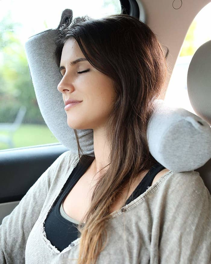 model sleeps with head on bendy boodle shaped travel pillow