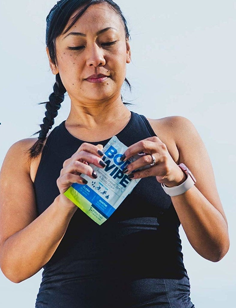 model in fitness clothing opening a package of body wipes