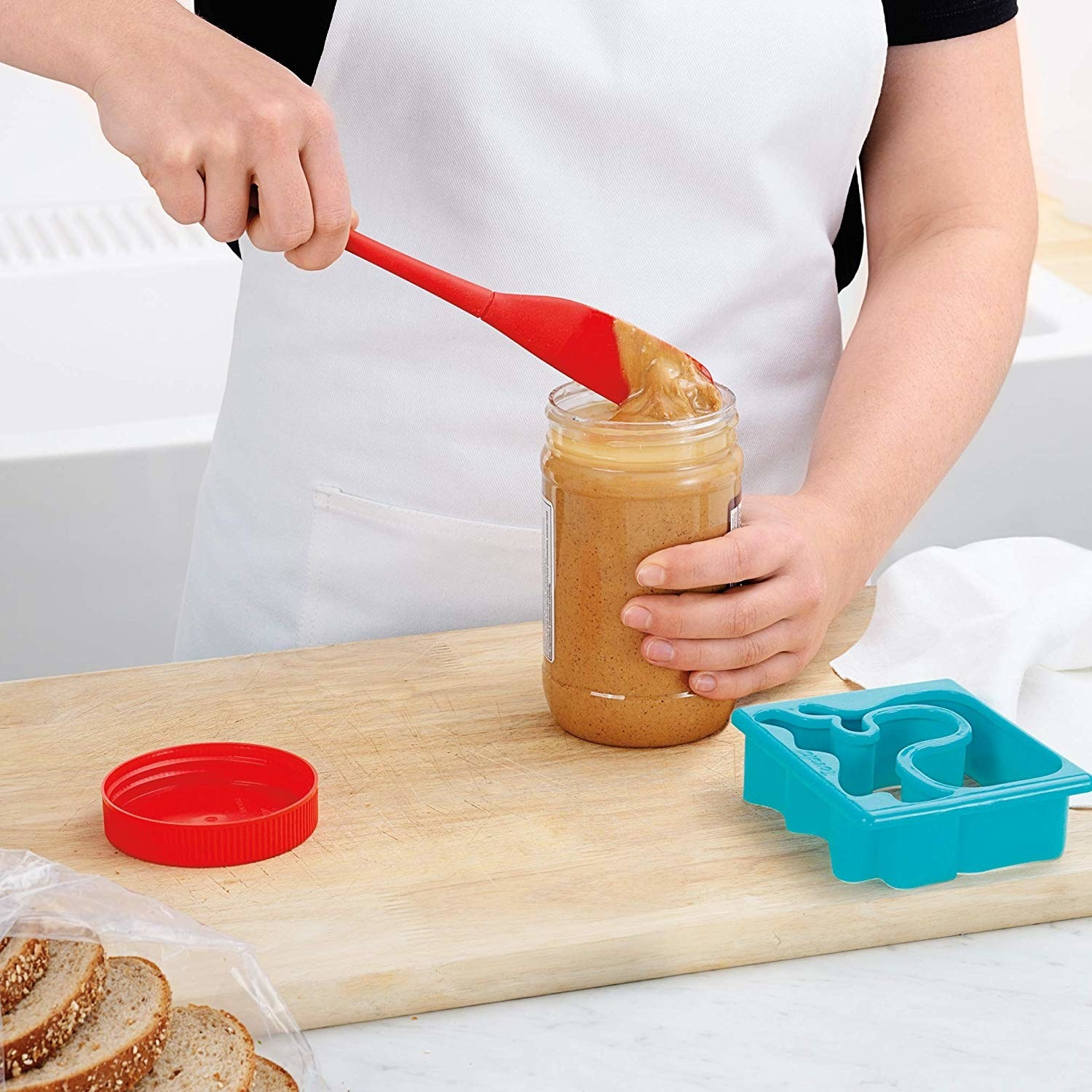 Model scooping peanut butter with the scraper