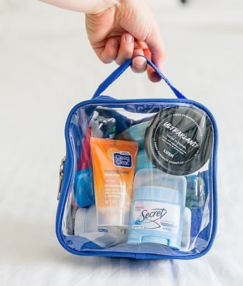 hand holding the clear square bag with blue trim filled with toiletries