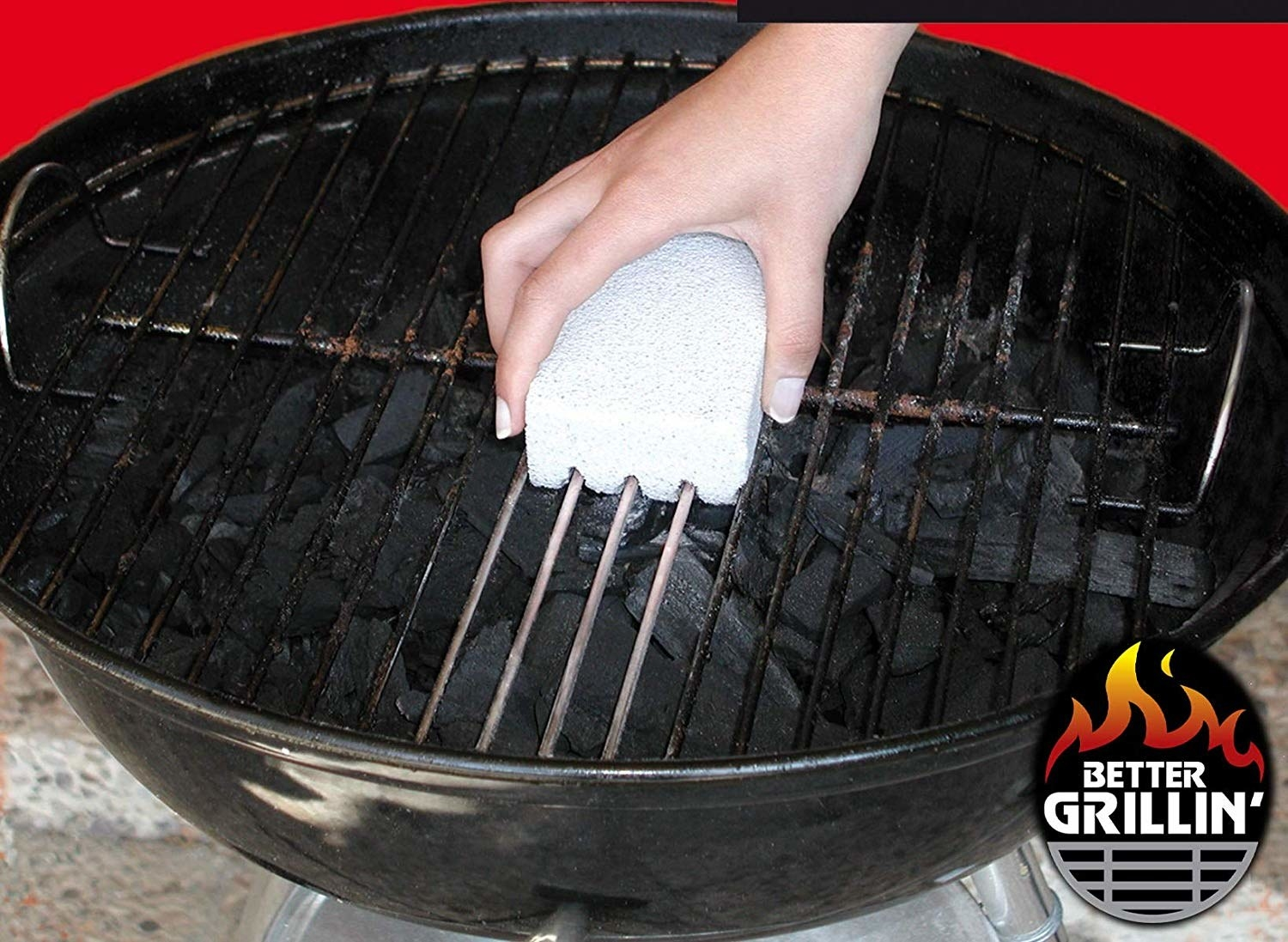 person using the stone to clean a grill