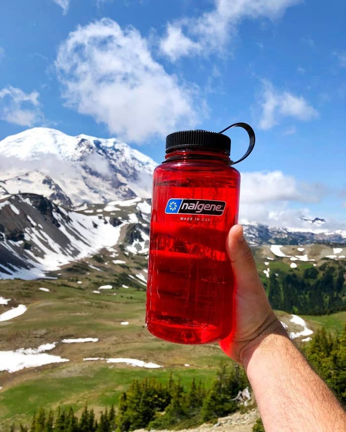 person holding red nalgene with mountain in the background