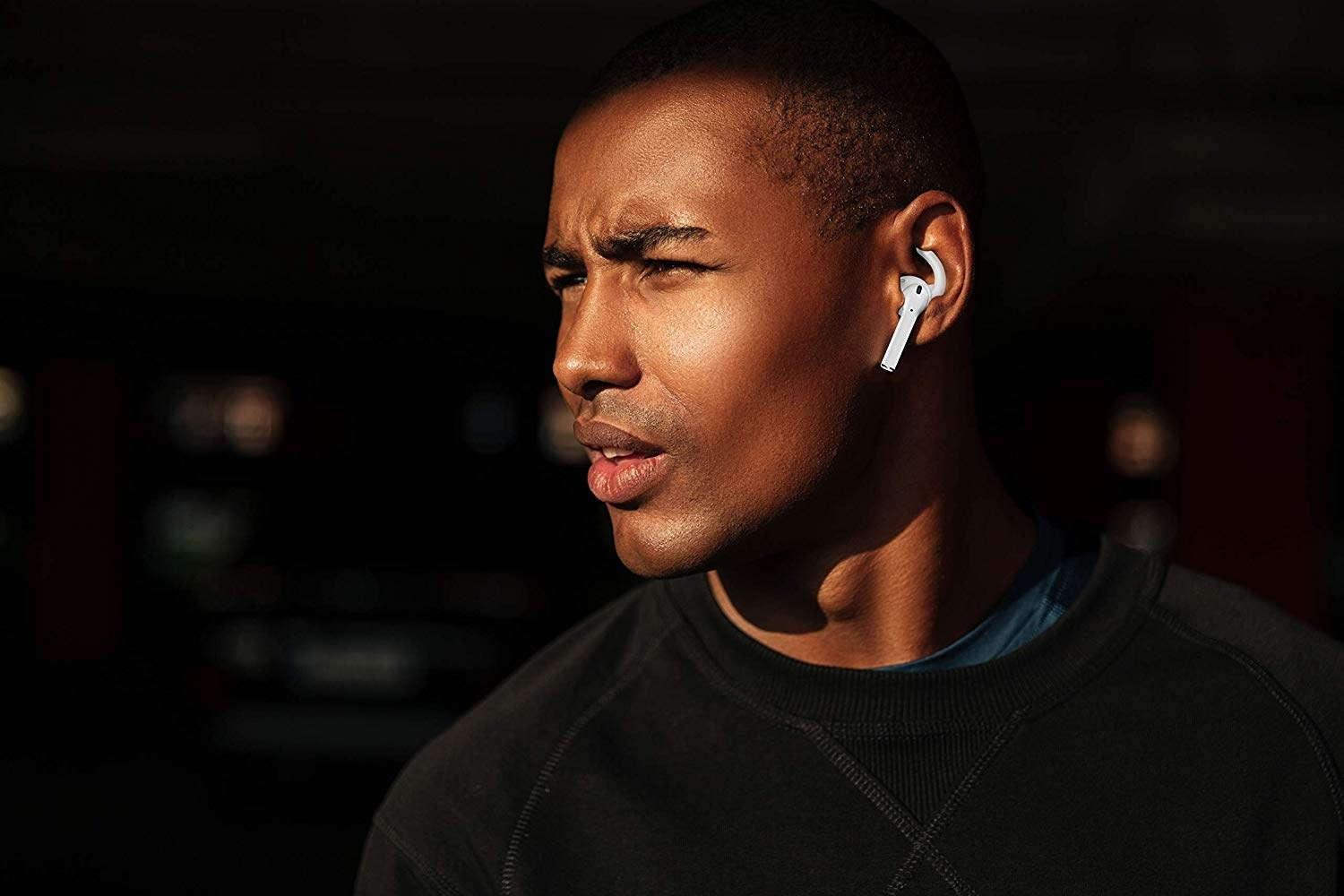 Model with the grips holding a pair of wireless earbuds in their ears