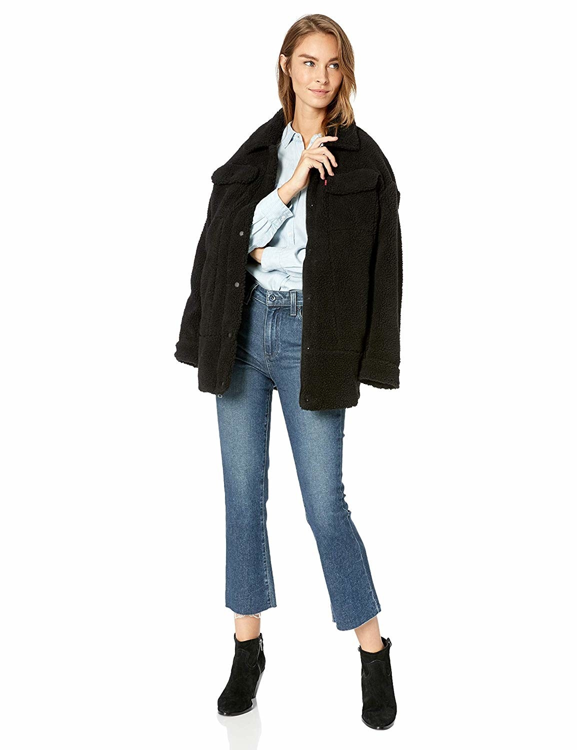 Model wearing the oversized black fuzzy jacket with pockets on both side of the chest draped over their shoulder