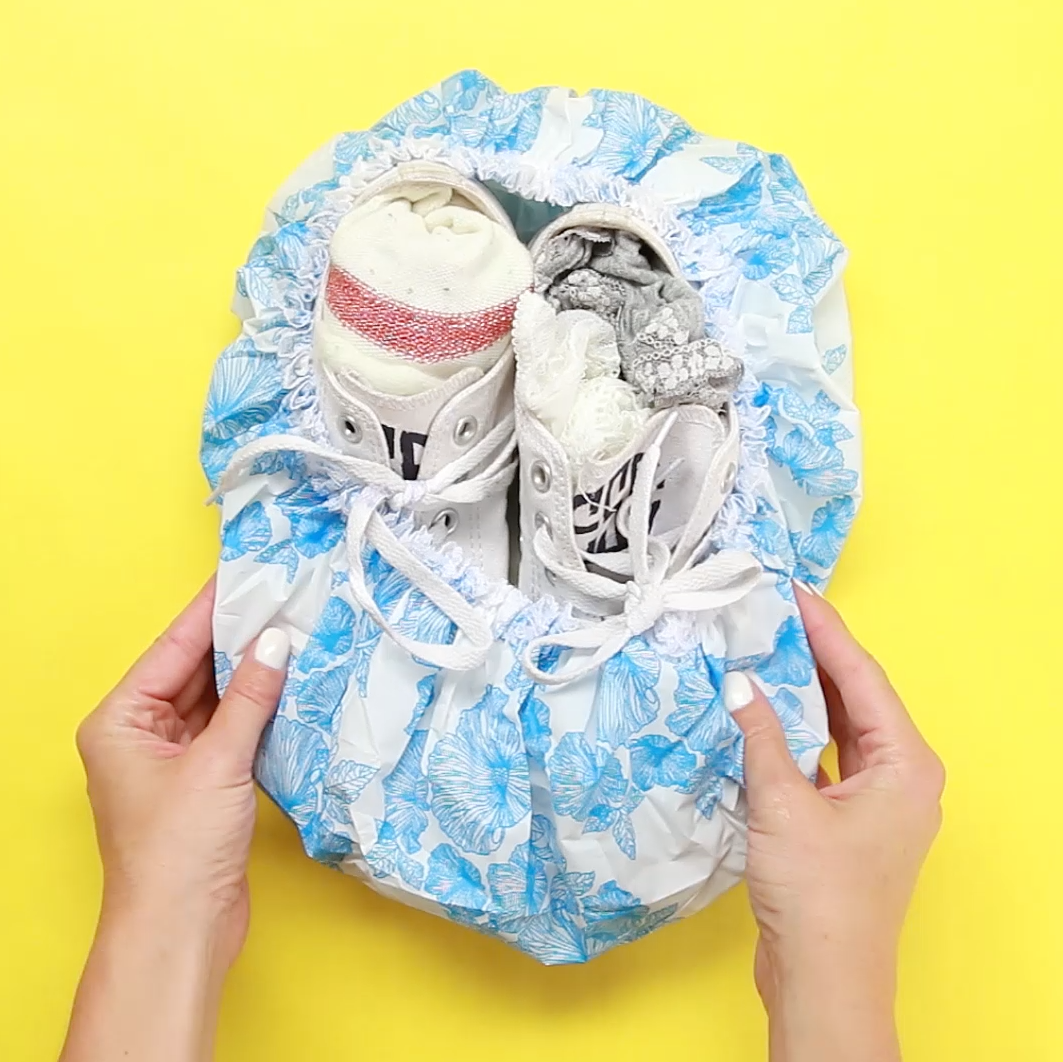 A pair of sneakers in a shower cap, each stuffed with socks