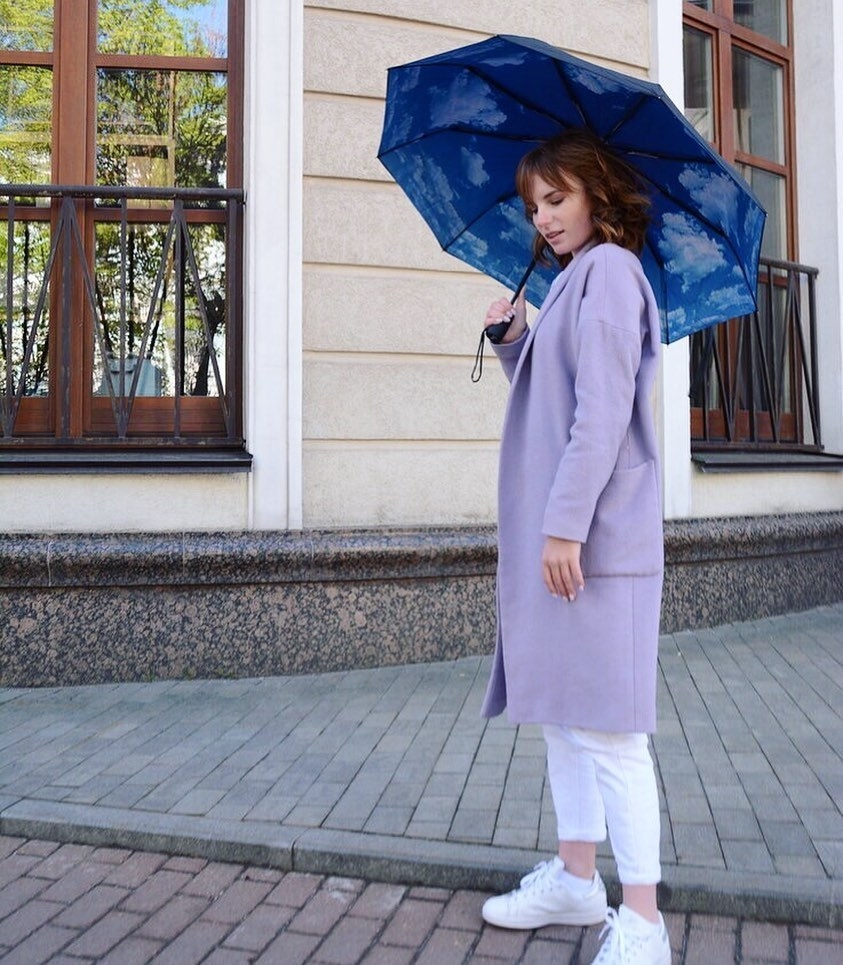A photo of a model using the umbrella in blue with a cloud design on the inside of the umbrella