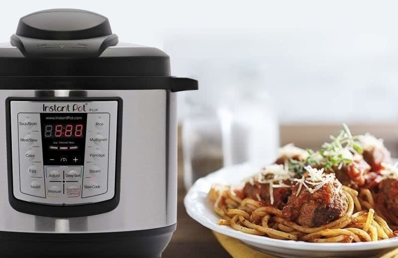 The Instant Pot next to a bowl of spaghetti and meatballs