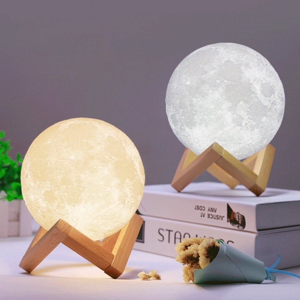 Moon lamps kept on a surface and books.
