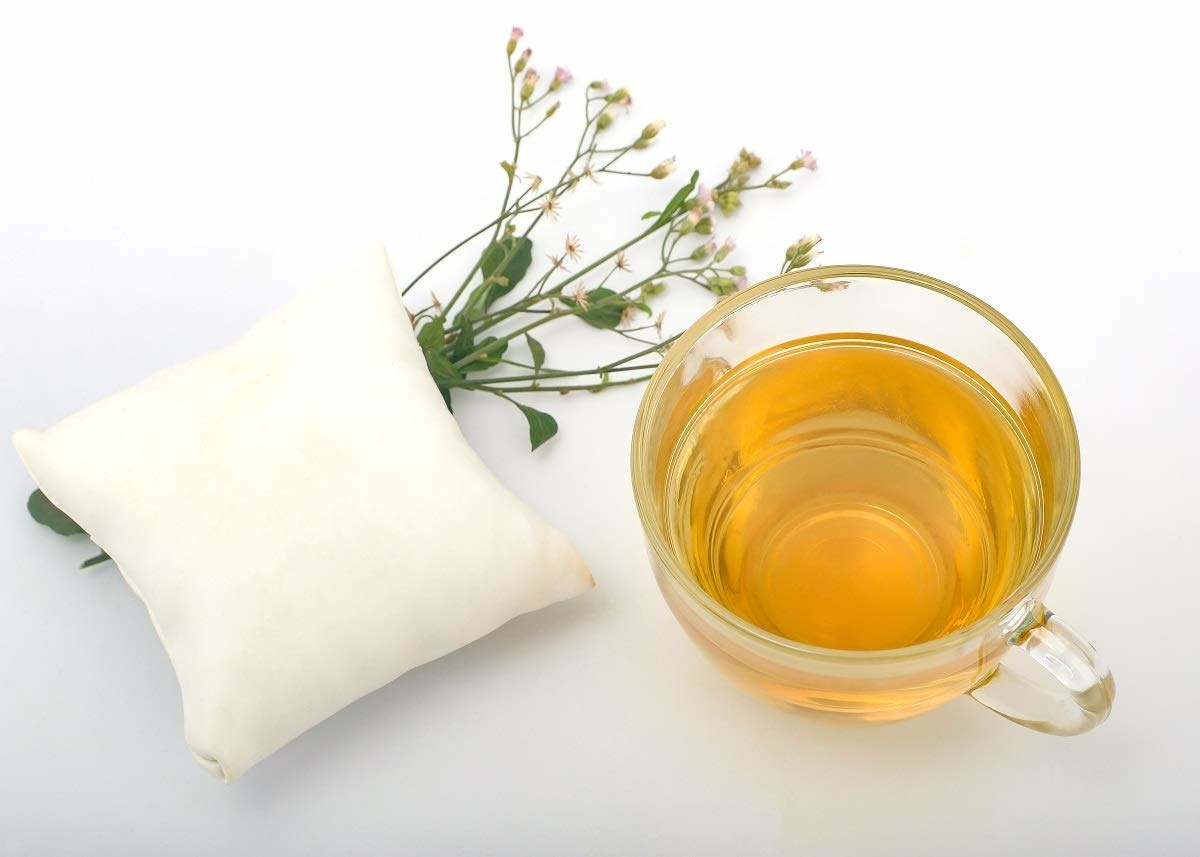 A cup of tea beside herbs and a tiny pillow.