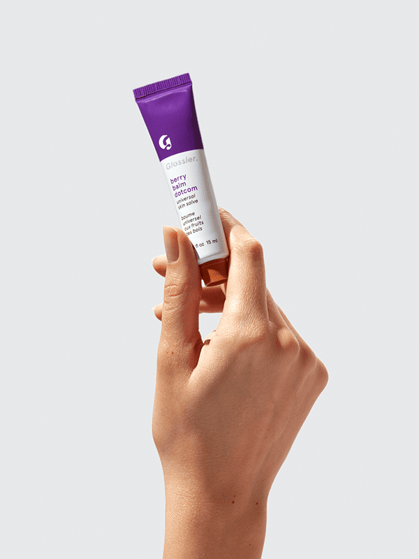 A person holding the very berry-scented balm dot com tube