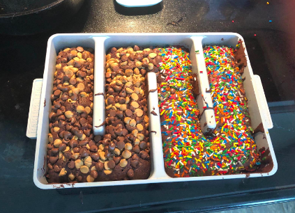Reviewer's homemade brownies baked inside pan with one side covered in peanut butter chocolate chips and the other side with sprinkles