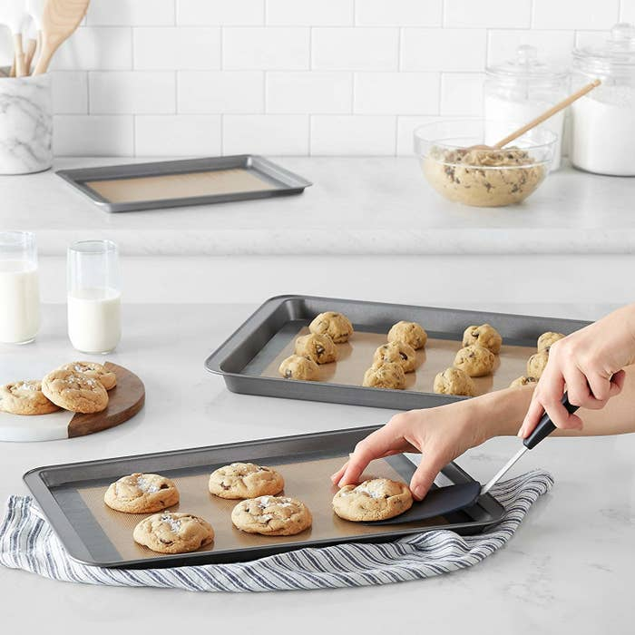 A person picking up a cookie from a baking tray with a kitchen spatula The baking tray is line with a silicone mat