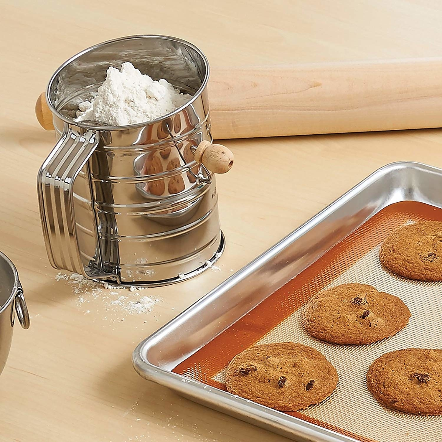 A small metal sifting cup filled with flower and placed next to a tray of cookies