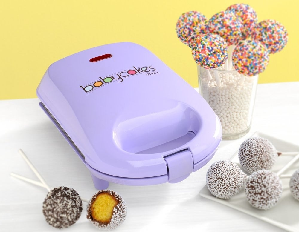A cake pop maker that looks similar to a waffle iron with cake pops on sticks next to it