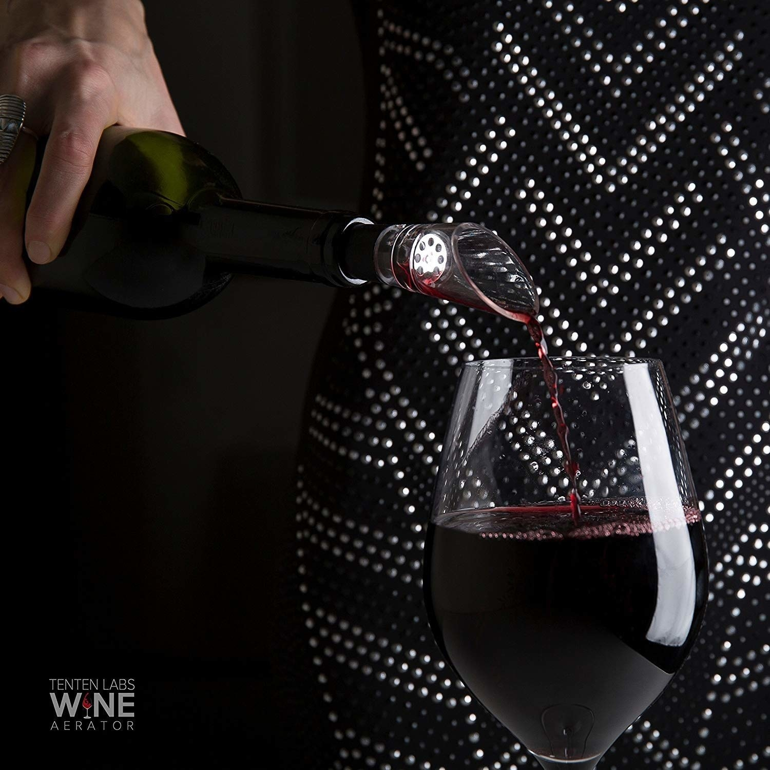 A model pours red wine into a wine glass using the TenTen wine aerator