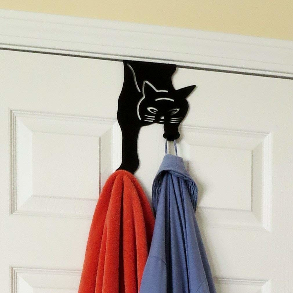 the cat hanger over a door holding a shirt and towel