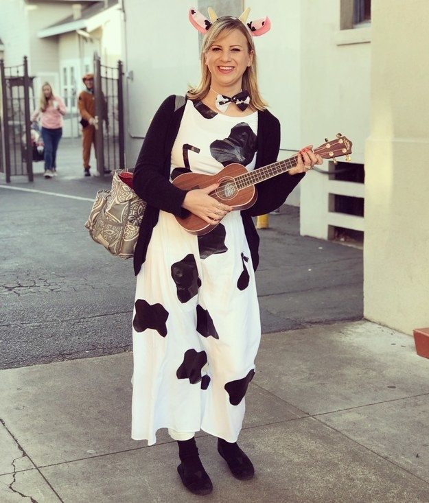 A woman in a cow-print dress carrying an ukulele