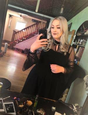 reviewer wearing the black mesh dress