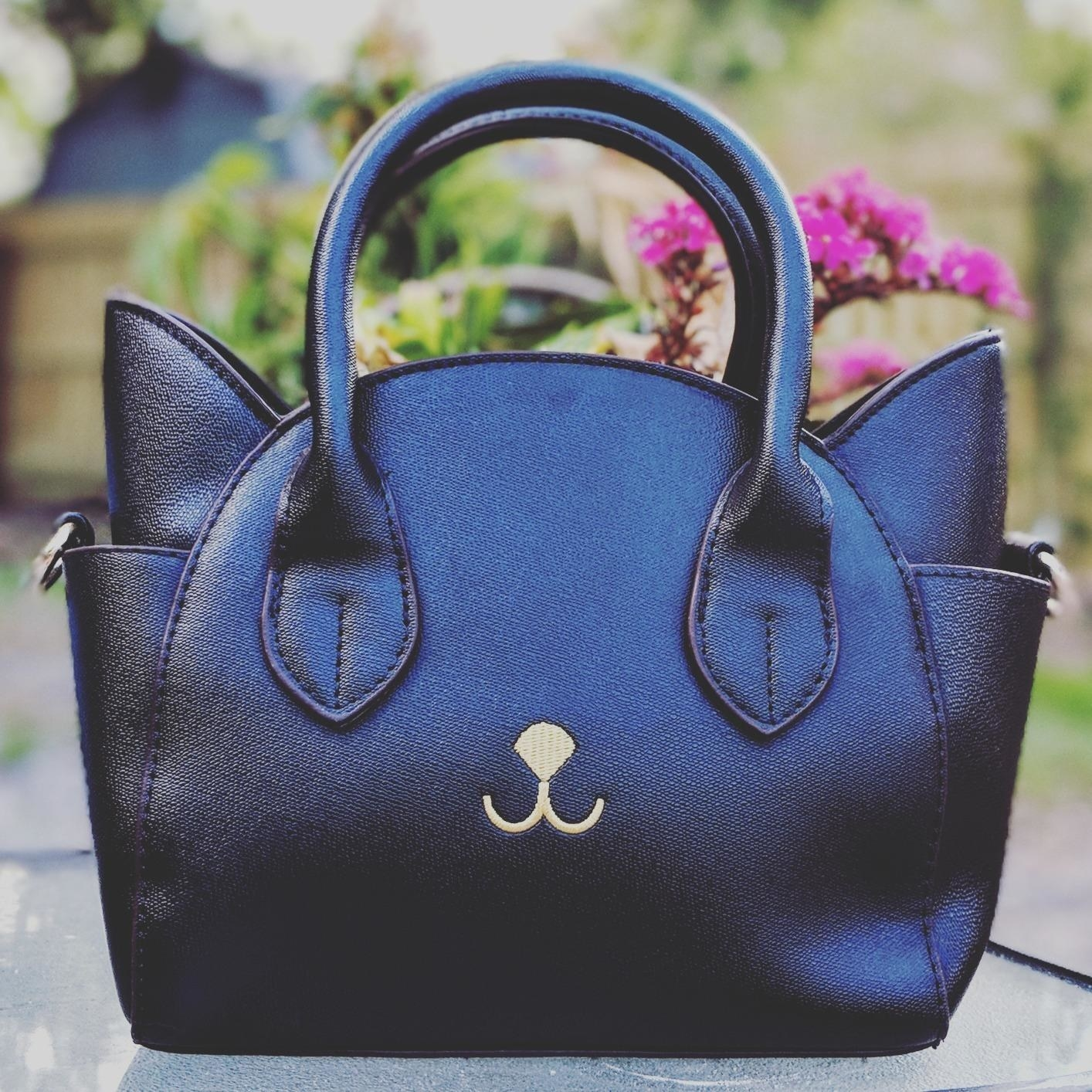Reviewer pic of the purse in black with ears on either side and pockets below them and a small white nose and mouth on the front with the ends of the straps looking like eyes.