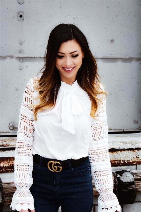 Reviewer wearing the blouse in white with a tie around the neck and lace sleeves with elastic near the end and flared hem.