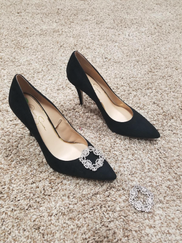 A reviewer's plain black heels with a square rhinestone clip on one pair