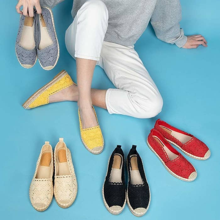 a model wearing a yellow pair of the espadrilles, holding another blue pair, and with three other pairs sitting by their feet