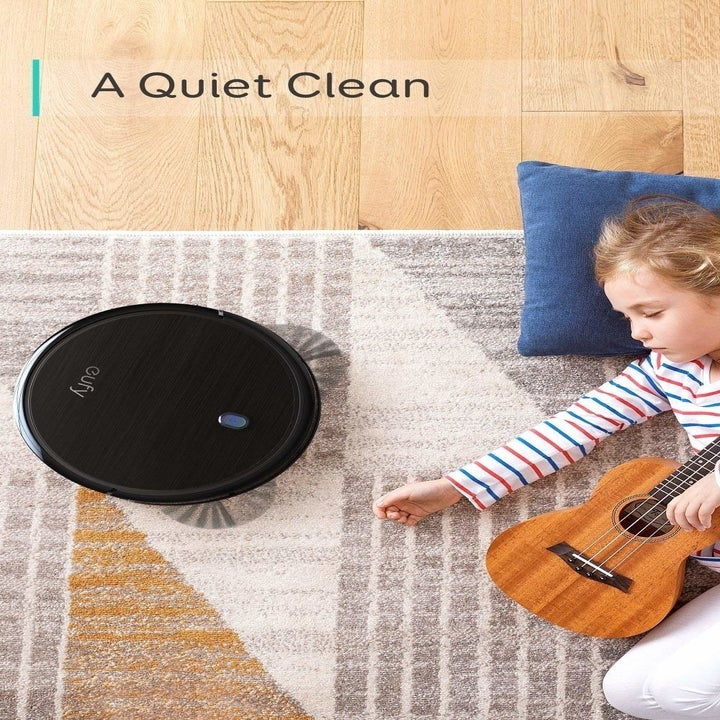 Child napping on rug with vacuum nearby