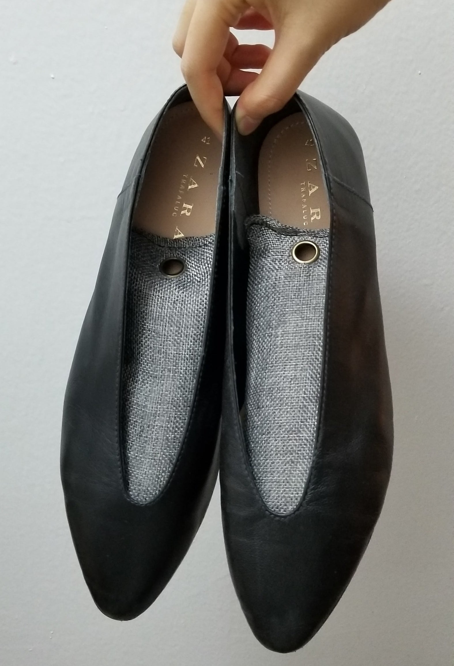 A person holding a pair of flat shoes with deodorizing bags inside them