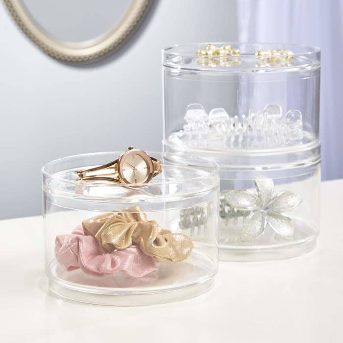 Circular see-through containers holding hair accessories. The containers can stack on top of each other