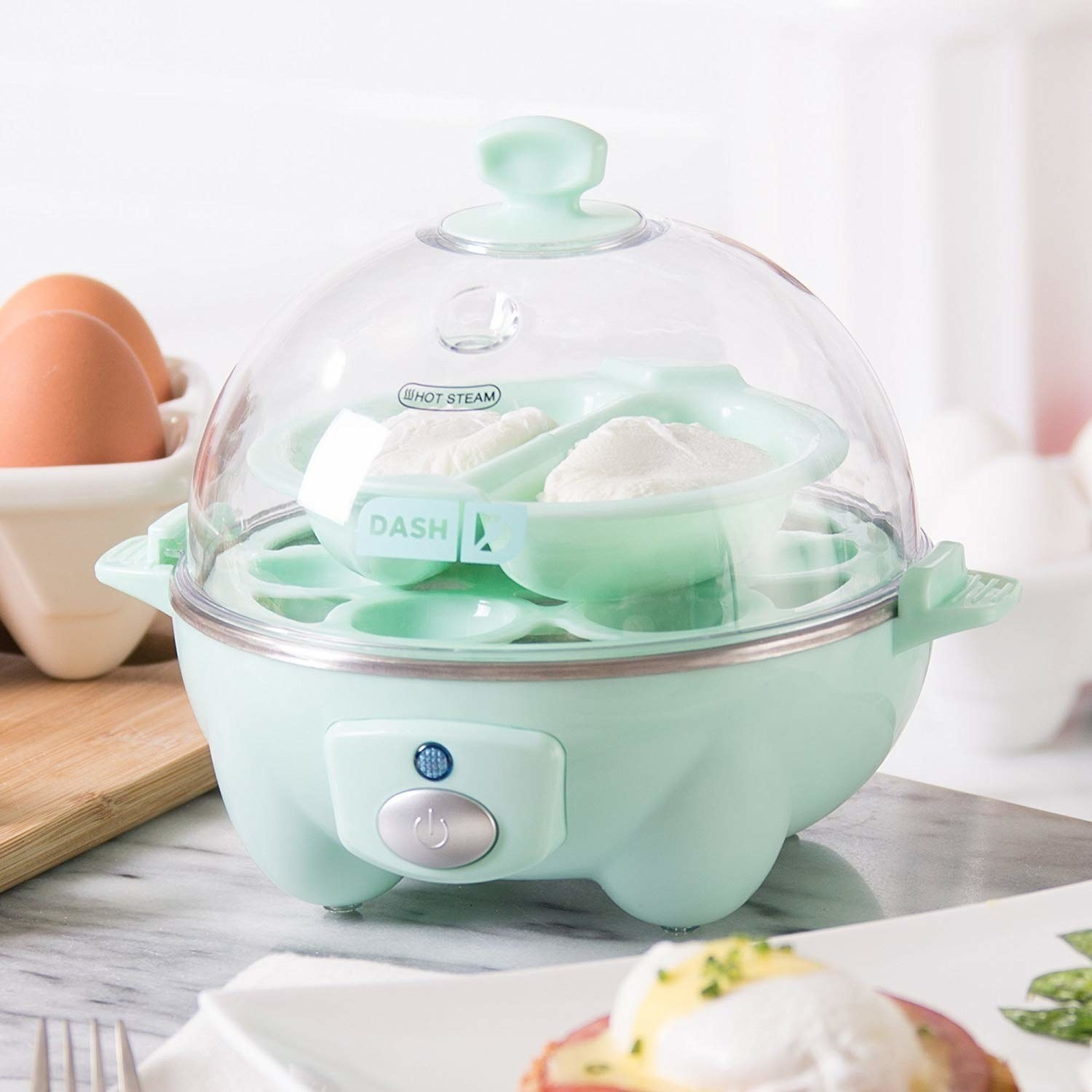 The little domed egg cooker, which has a mint base with a power button and a clear top that snaps on; two eggs are poaching in a tray