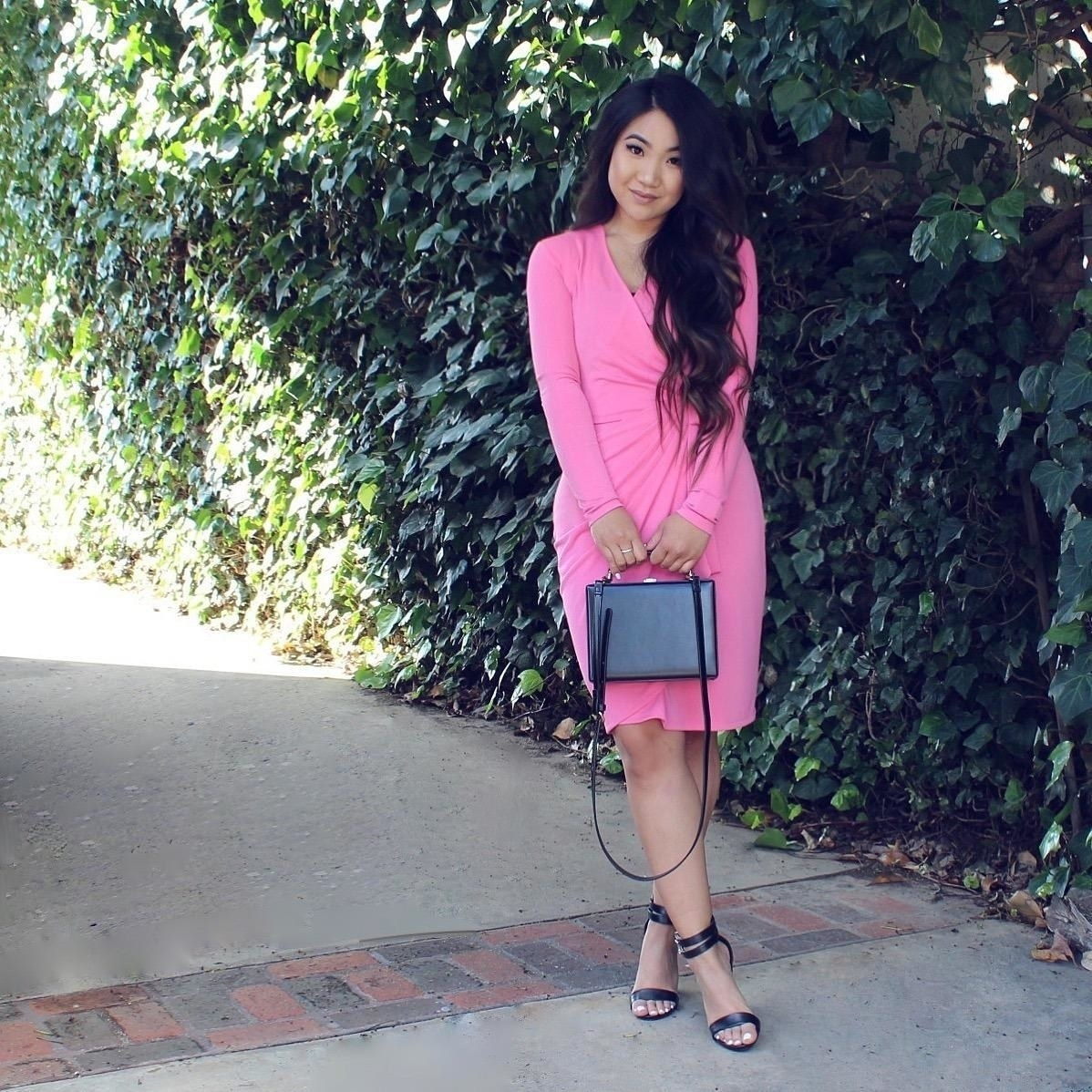 Reviewer wearing the long-sleeved wrap dress in bright pink.