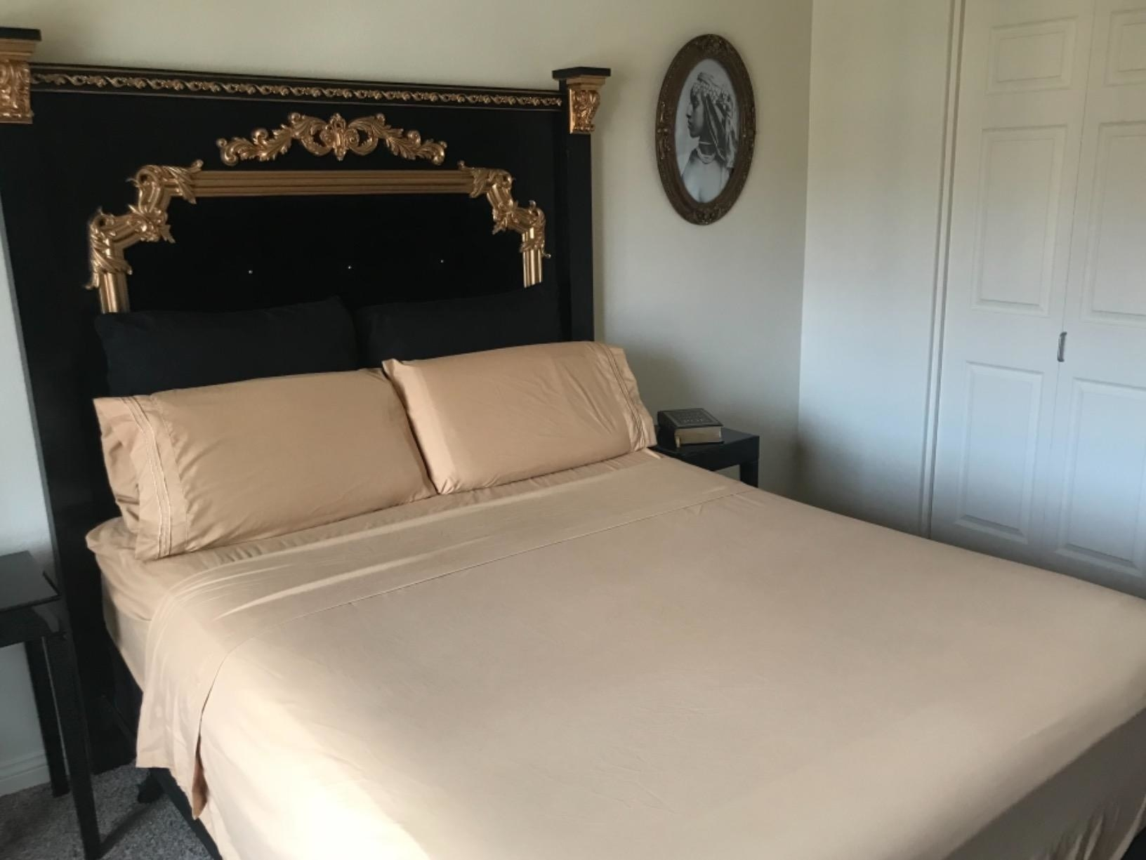 A reviewer showing dark beige-colored sheets neatly fitted across their bed