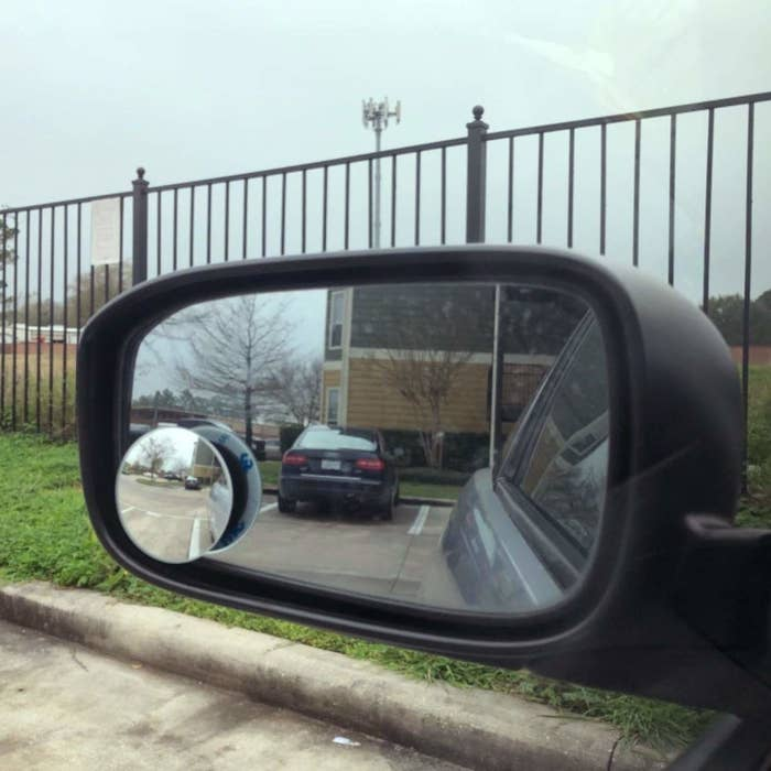 Car side mirror with circular mirror sticker in the corner, giving a better view of behind the vehicle