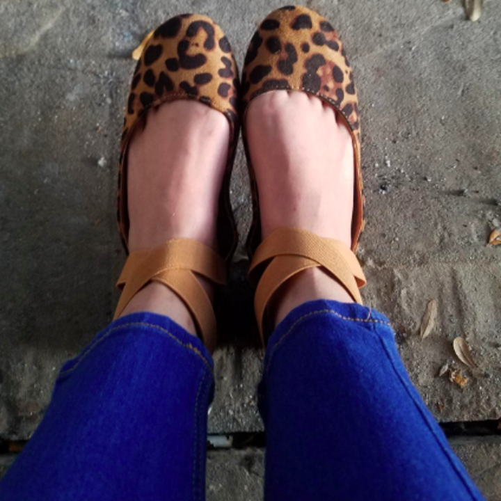 A reviewer wearing the flats with criss-cross ankle straps in leopard