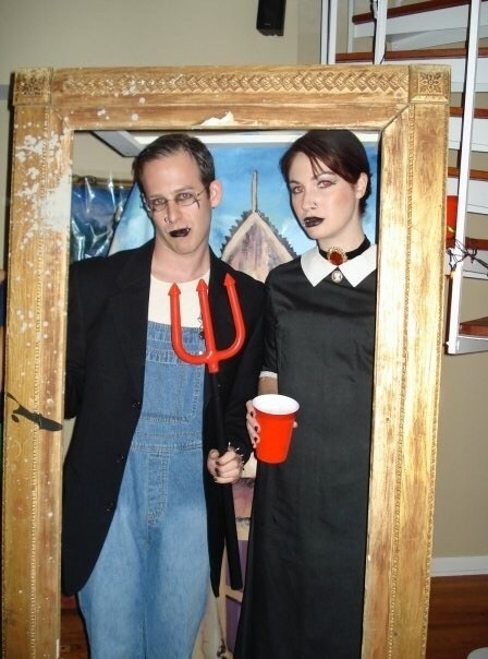 """Two people inside a large frame recreating the """"American Gothic"""" painting with goth clothes and makeup"""