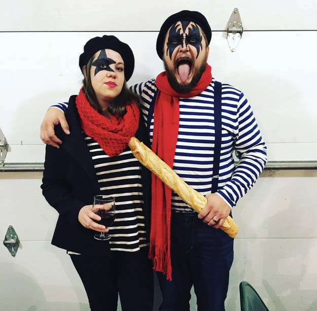 A man and woman with Kiss face paint wearing berets, striped tees, and holding wine and a baguette