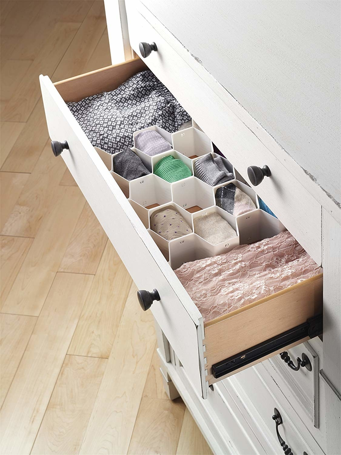 The organizer with honeycomb-shaped spaces inside a drawer