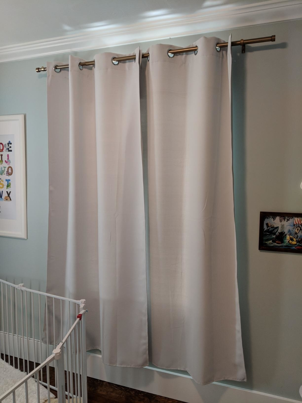 A reviewer showing the curtains over a window