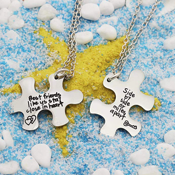 A pair of necklaces with metal puzzle pieces One says best friends like us stay close in heart The other says side by side or miles apart