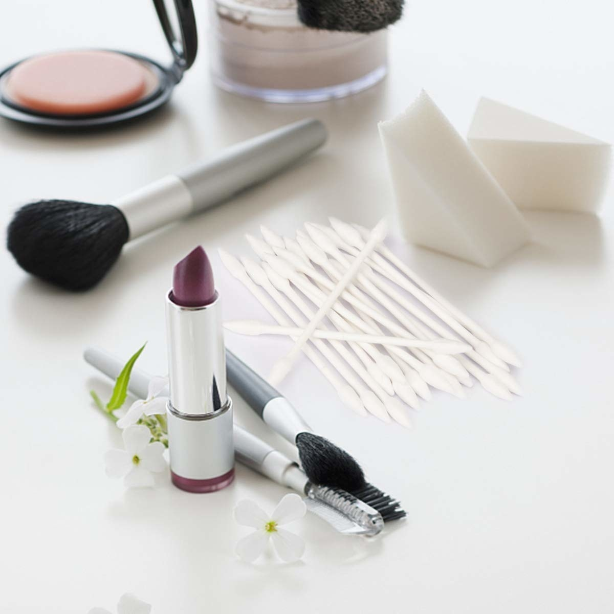 A pile of pointed cotton swabs next to makeup brushes, sponges, and a tube of lipstick